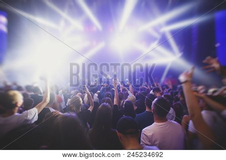 A crowded concert hall with scene stage lights, rock show performance, with people silhouette and ha