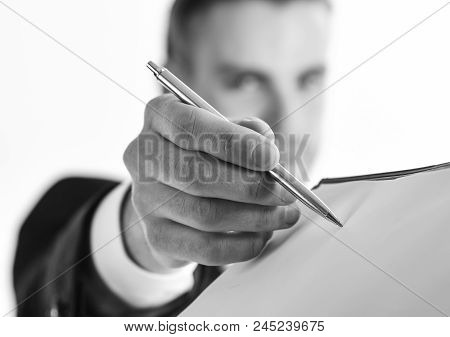 Businessman Signs Document By Pen On White Background. Signing Documents Concept. Man With Serious F