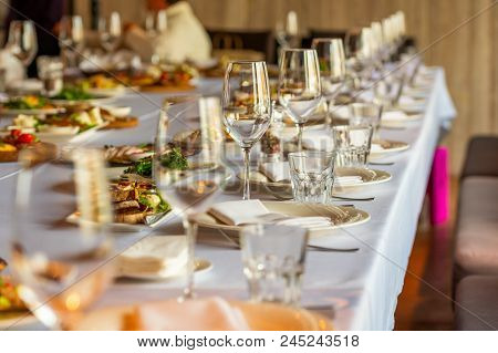 Crystal Wine Glasses On A Served Banquet Table With Salads And Snacks