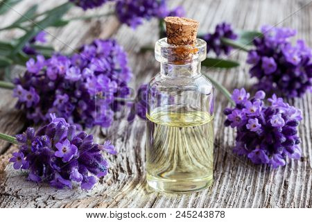 A Bottle Of Essential Oil With Fresh Lavender On A Rustic Wooden Background