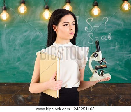 Lady Scientist Holds Book And Microscope, Chalkboard On Background, Copy Space. Lady In Formal Wear