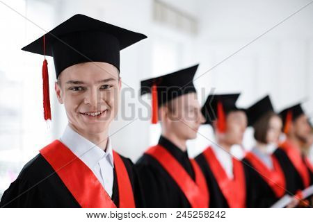 Student in bachelor robe indoors. Graduation day