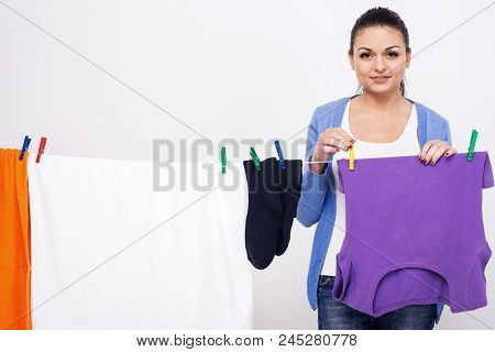 Young Woman Hangs Clothes On Dryer For Clothes After Washing. Womens Hands And Wet Clothes. Post Clo