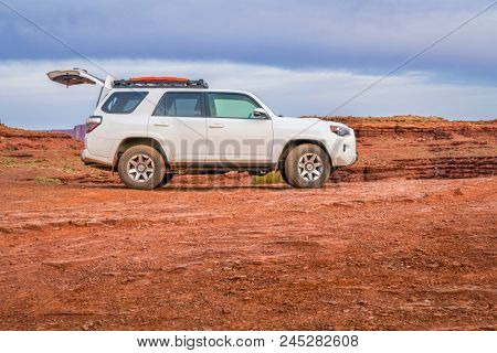 Moab , UT, USA - May 6, 2018:  Toyota 4runner SUV (2016 trail edition, stock vehicle) with an opne gate and recovery ladders on roof racks on a desert trail before sunrise in the Moab area.