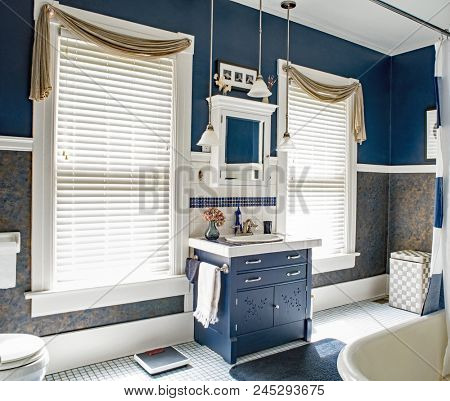 Dayton, Ohio, USA - June 13, 2018: Updated blue & white bathroom of a one hundred-year-old home with antique dresser for sink vanity.