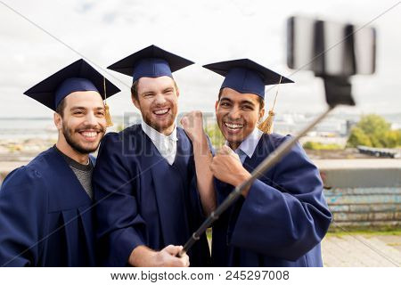 education, graduation, technology and achievement concept - group of happy international students in mortar boards and bachelor gowns taking photo by selfie stick outdoors and celebrating