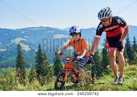 Verkhovyna, Ukraine - August 19, 2017: Young Dad In Biker Outfit Teaches Preschool Boy To Ride A Bik