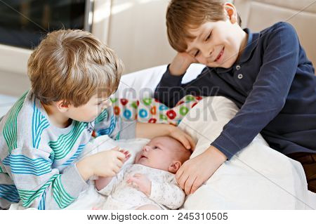 Two Little Kids Boys With Newborn Baby Girl, Cute Sister. Siblings. Brothers And Baby Playing With C