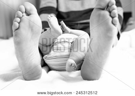 Closeup Of Huge Feet Of Father And Little Newborn Baby. Big Feet Of Adult And Tiny Legs Of Child. Ha
