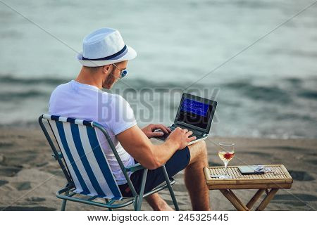 Man Working With Computer On The Beach. Freelancer Working