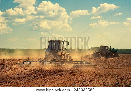 Two Tractors With A Plow In A Field At Sunset. Preparing Land For Sowing. Agricultural Works At Farm