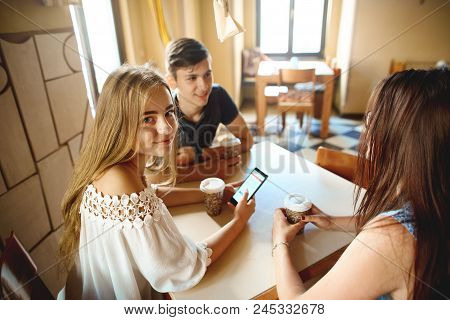 Young Girl With Girlfriends Sitting At Cafe Table, Talking And Smiling. Group Of Friends Enjoying In