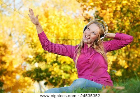 Smiling young attractive woman with headphones listening music in park at fall outdoors