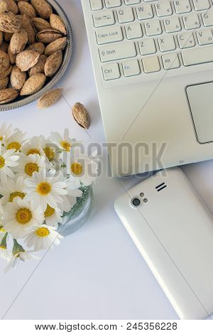 Workspace With Computer At Home , A Desk With Flowers And White Smartphone. Near Almonds . Woman's M