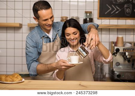 Smiling Young Couple In Aprons Preparing Coffee Together In Cafe