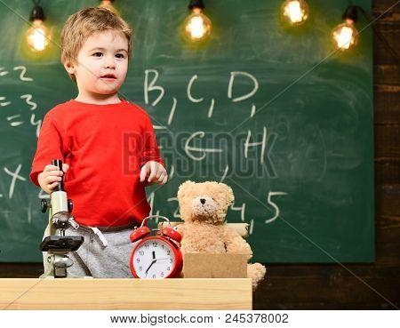 Kid Boy Near Microscope In Classroom, Chalkboard On Background. First Former Interested In Studying,
