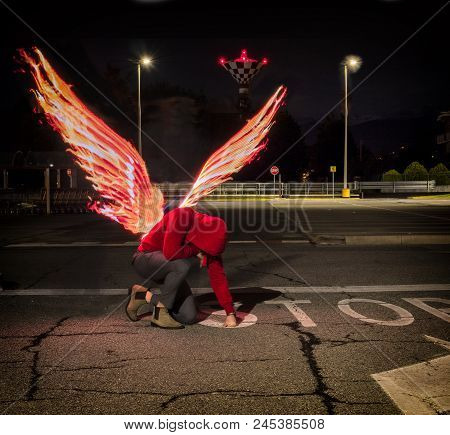 Fallen Male Angel Kneeling In City Parking Lot, With Fire Wings Spreading From His Back. Unrecogniza