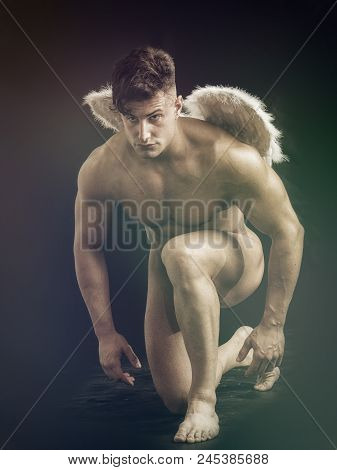Fallen Naked Male Angel Sitting In Dark With White Feather Wings Spreading From His Back. Angelic Na