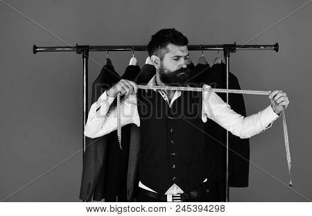 Man With Beard Holds Measuring Tape. Tailor Cuts And Sews Suit. Young Man In Tailoring Shop Makes Me