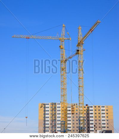 yellow construction cranes against the blue sky