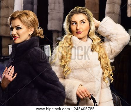 Women In Fur Coats With Bags In Fur Shop. Girls With Mysterious Faces In Black And White Fur Coats H