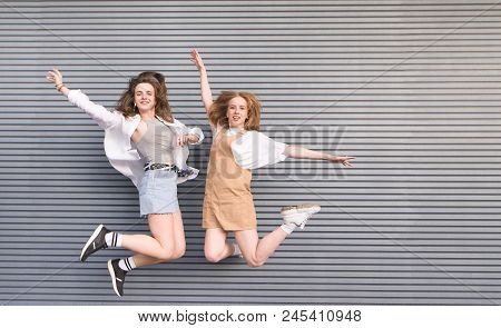 Happy Young Girls Jumping With Their Hands Raised On A Gray Dark Background. Two Smiling Girlfriends