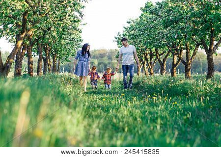 Happy Young Family Spending Time Together Outside In Green Nature. Parents Playing With Twins Outsid