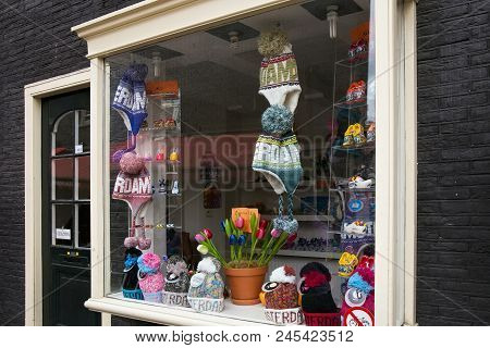 Amsterdam, Netherlands - June 25, 2017: Storefront Of Souvenir Shop With Different Knitted Hats In T