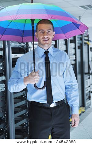 poster of young handsome business man  engineer in  businessman hold  rainbow colored umbrella in server datacenter room  and representing security and antivirus sofware protection concept
