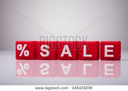 Red Cubic Blocks With Percentage Symbol And Word Sale On Reflective Background