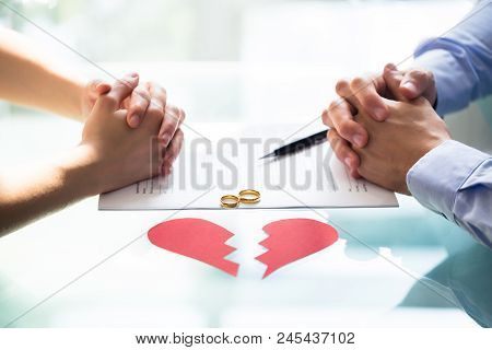 Couple's Hand On Divorce Paper