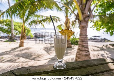 Tropical Pina Colada Cocktail Drink With Pineapple Garnish In Glass With Straw At Exotic Beach At Le