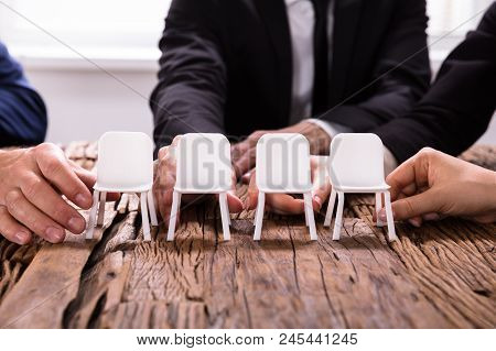 Businesspersons's Hands Arranging Chairs In A Row
