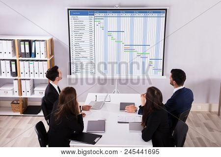 Group Of Businesspeople Analyzing Gantt Chart On Projector In Office