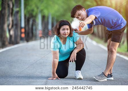 Trainer Encouragement To Fat Woman Who Sitting On Ground And Point His Hand To The Target