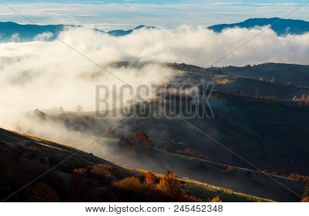 Cloud Inversion In Autumn Mountains. Beautiful Nature Scenery. Fog Rolling Above The Rural Fields In