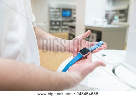 Man In The Electronics Store Holds A Smart Watch With A Blue Strap In His Hands. Buy Smart Watch In