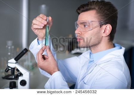 Strange Substance. Young Unshaken Handsome Practitioner Working In The Laboratory Sitting And Observ