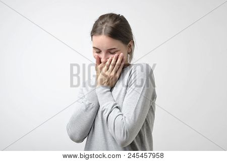 Pretty Caucasian Girl In Simple Pulover Is Shy To Hear A Compliment. She Is Hiding Her Face.
