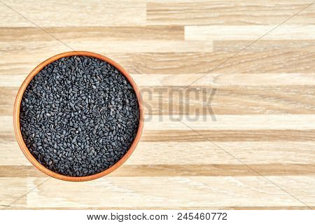 Black Sesame Seeds In A Clay Bowl On Stripped Wooden Textured Background, Close-up, Top View. Some C