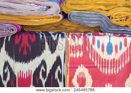 Ornament Ikat Khan Atlas. Background Of Silk Fabric With Oriental Ornaments. Uzbek Silk With Ornamen