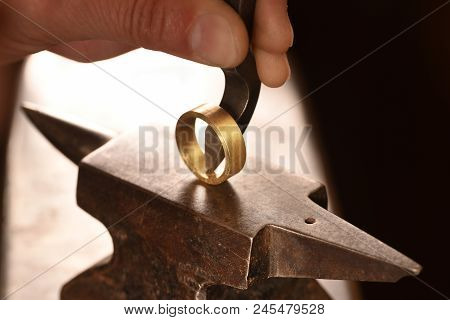 hand of a goldsmith punches a hallmark into a golden ring on an anvil, close up with copy space,  focus, narrow depth of field t-shirt