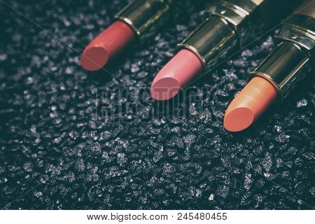 Close-up Of Lipstick On Anthracite Surface. Trendy Lip Make-up, Copy Space. Side View, Shallow Depth