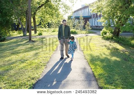Father With Daughter Walking In Park At Sunny Day.  Dad With Little Girl Outdoor. Family Authentic L