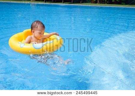 Cute Little Asian 2 Years Old Toddler Boy Child Having Fun Playing With Inflatable Swim Ring In Outd