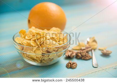 Tasty Cornflakes Witt Walnut In Glass Bowl On Blue Background. Corn Flakeshealthy Breakfast-cornflak