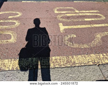 Commuter At A Bus Stop, Lone Figure Shadow On The Road Waiting