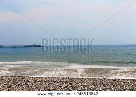 Rocky Beach By The Sea With Waves Hitting Seashore. Blue Sky In The Background. Nature Photography W
