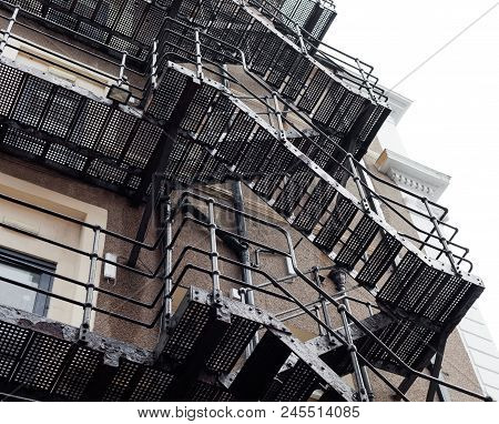 Frog Perspective On The Large Old Building With Metal Stairs. Building Made Of Bricks. Fire Stairs O