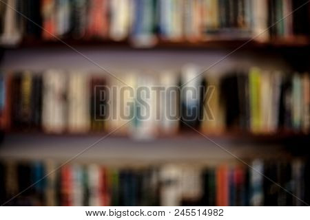 Shelves With Books In A Blurred Background. Learning Concept With Blurred Library Books On The Shelv